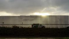 A U.S. Border Patrol vehicle drives by the 18-foot (five-metre) high rusty steel barrier along the U.S.-Mexico border at sunset in Brownsville, Texas September 2, 2014. REUTERS/Rick Wilking