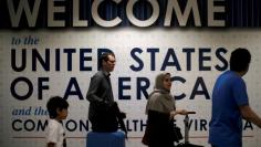 FILE PHOTO: International passengers arrive at Washington Dulles International Airport after the U.S. Supreme Court granted parts of the Trump administration's emergency request to put its travel ban into effect later in the week pending further judicial