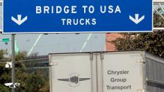 FILE PHOTO: A commercial automotive supplier truck passes under a sign leading to the Ambassador bridge crossing over to Detroit, Michigan from Windsor, Ontario