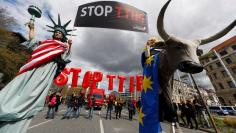 The flag of the USA flutters over a hall of the Hanover Fair decorated with a banner supporting the free trade agreement TTIP (Transatlantic Trade and Investment Partnership) in Hanover, Germany April 25, 2016.  REUTERS/Wolfgang Rattay