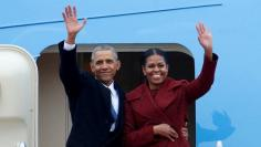 FILE PHOTO - Former president Barack Obama waves with his wife Michelle as they board Special Air Mission 28000, a Boeing 747 which serves as Air Force One, at Joint Base Andrews, Maryland, U.S. on January 20, 2017.   REUTERS/Brendan McDermid/File Photo