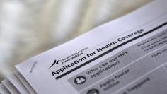 "FILE PHOTO - The federal government forms for applying for health coverage are seen at a rally held by supporters of the Affordable Care Act, widely referred to as ""Obamacare"", outside the Jackson-Hinds Comprehensive Health Center in Jackson, Mississippi"