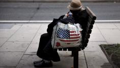 A homeless woman sits on a bench few blocks away from the White House in downtown Washington