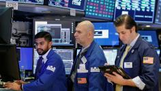FILE PHOTO - Traders work on the floor of the New York Stock Exchange (NYSE) in New York, U.S., January 26, 2018. REUTERS/Brendan McDermid