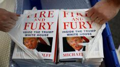 A shop worker opens a package containing copies of Michael Wolff's book 'Fire And Fury' as they go on sale inside a branch of the Waterstones book store in Liverpool, Britain, January 11, 2018. REUTERS/Phil Noble