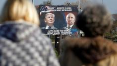 FILE PHOTO: A  billboard showing a pictures of US president-elect Donald Trump and Russian President Vladimir Putin is seen through pedestrians in Danilovgrad, Montenegro, November 16, 2016. REUTERS/Stevo Vasiljevic/File Photo