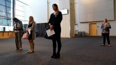 Attendees carry their resumes at a job fair in Washington