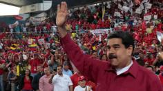 Venezuela's President Nicolas Maduro waves during a pro-government rally with workers of state-run oil company PDVSA, in Barcelona