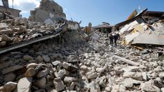 Rescuers work on collapsed buildings following an earthquake in Amatrice